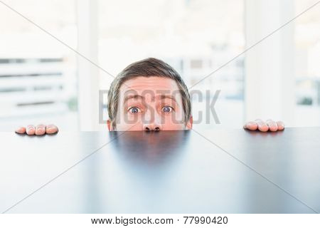 Nervous businessman peeking over desk in his office