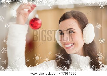 Pretty brunette with ear muffs holding bauble against fir tree forest and snowflakes
