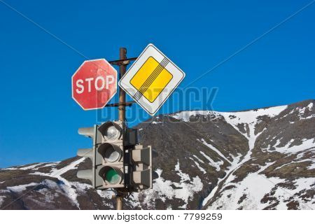 Stop! Road Signs And Traffic Light On Blue Sky