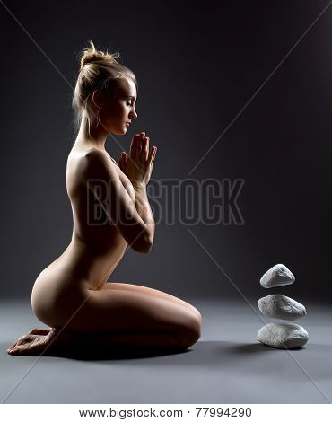 Beautiful nude girl mentally makes stones to fly
