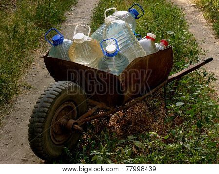 wheelbarrow full of plastic bottles with artesian water