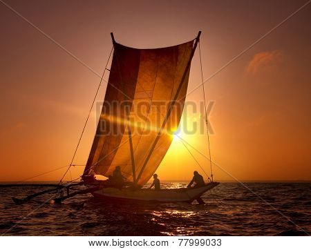 Fishermen on a catamaran at Sunset.