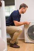 pic of handyman  - Focused handyman fixing air conditioning in a new house - JPG