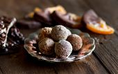 stock photo of truffle  - Chocolate truffles and orange slices in dark chocolate on a wooden table  - JPG