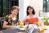pic of hispanic  - A senior hispanic woman having breakfast outdoors with a daughter - JPG