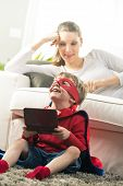 foto of playtime  - Little superhero boy playing videogames and mother lying down on sofa in the living room - JPG
