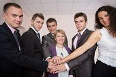 stock photo of joining hands  - Six business people join hands and smiling - JPG