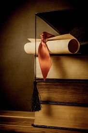 stock photo of scroll  - A stack of old books topped with a mortarboard and diploma scroll tied with red ribbon - JPG
