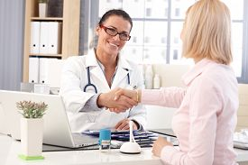 pic of stethoscope  - Happy female brunette doctor at medical office with patient - JPG
