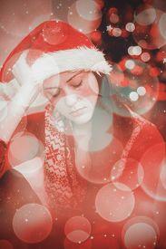 picture of sad christmas  - Festive brunette feeling sad at christmas against twinkling red and orange lights - JPG