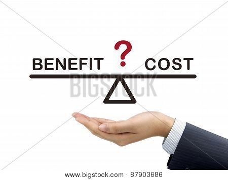 Balance Between Benefit And Cost Holding By Businessman's Hand