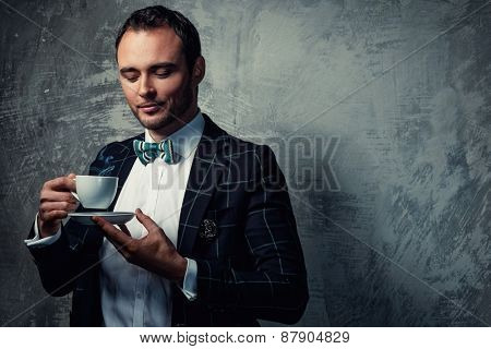 Sharp dressed fashionist with cup of coffee
