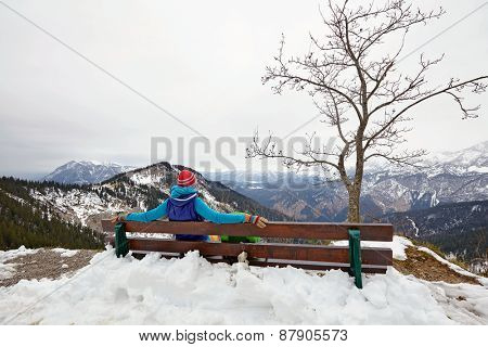 Rear view of female hiker sitting on wooden bench in snowy Alps with view over winter mountain landscape