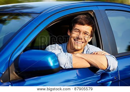 Portrait of young handsome smiling man in glasses looking out through open car window outdoor in sunny day
