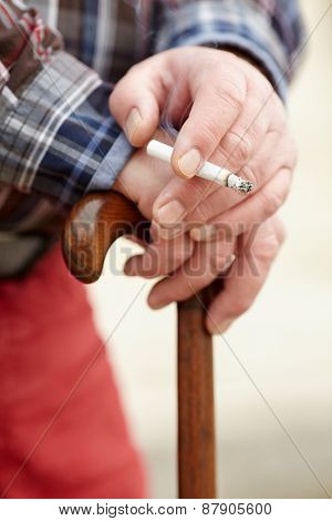 Close up of mature man hands with cigarette leaning on wooden walking stick outdoor