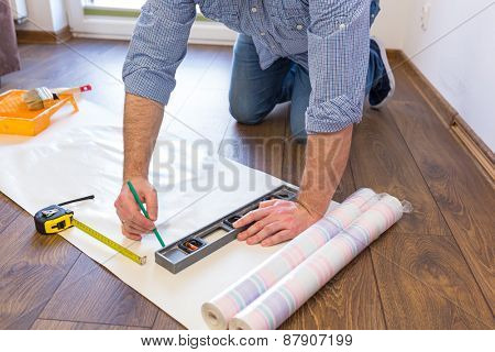 Handyman measuring wallpaper to cut