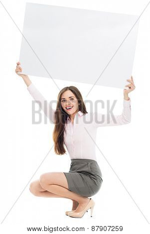 Woman crouching with blank sign