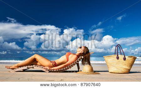 Woman in bikini lying on tropical beach at Seychelles