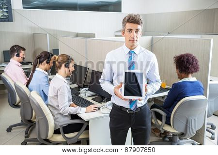 Portrait of confident manager holding tablet computer while customer service executives working in background at call center