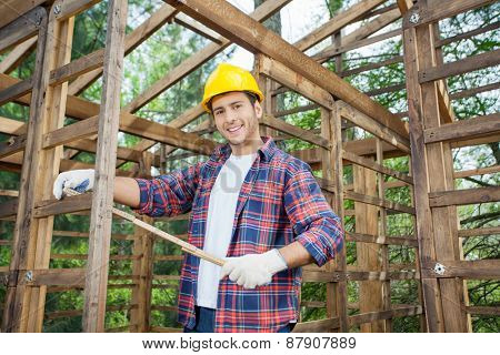 Portrait of happy carpenter holding measure tape in wooden cabin at construction site