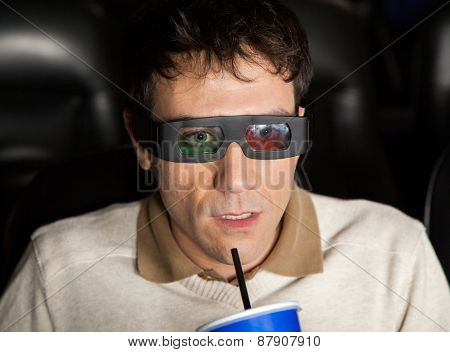 Closeup of shocked man drinking cola while watching 3D movie at cinema theater