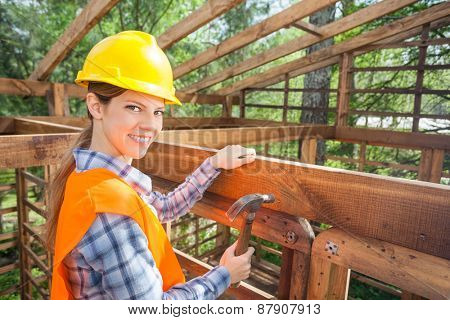 Side view portrait of happy female construction worker hammering nail on timber frame at site