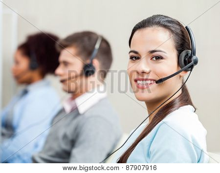 Portrait of smiling female customer service representative with colleagues in background at office
