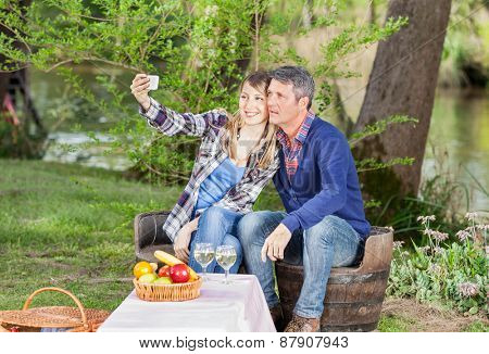 Smiling couple taking selfportrait through smartphone while sitting on chairs at campsite
