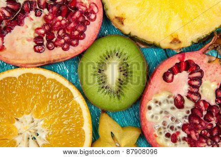 Colorful fruit slices on blue wooden surface