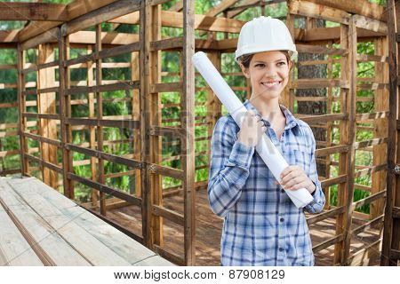 Happy female engineer looking away while holding blueprint in incomplete timber cabin at construction site