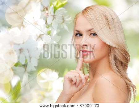 people, summer, spring, gesture and beauty concept - clean face of beautiful young woman pointing finger to her lips
