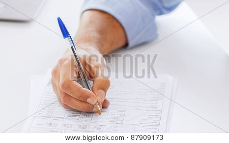 business, office, school and education concept - man filling tax form