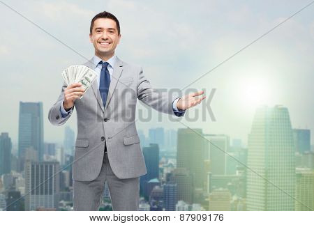 business, people and finances concept - smiling businessman with american dollar money over city background