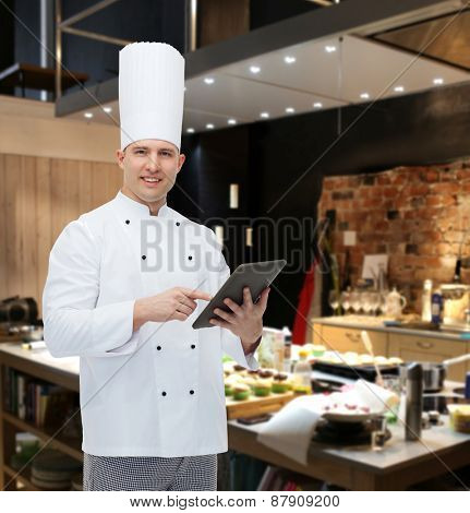 cooking, profession and people concept - happy male chef cook holding tablet pc computer over restaurant kitchen