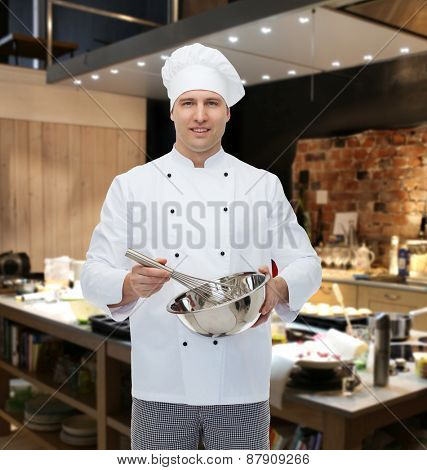 cooking, profession and people concept - happy male chef cook holding bowl and whipping something with whisk over restaurant kitchen