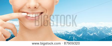 dental health, beauty, hygiene and people concept - close up of smiling woman face pointing to teeth over blue mountains background