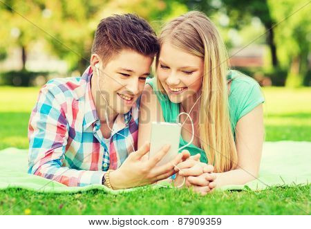 vacation, holidays, technology and friendship concept - smiling couple with smartphone and earphones making selfie in park