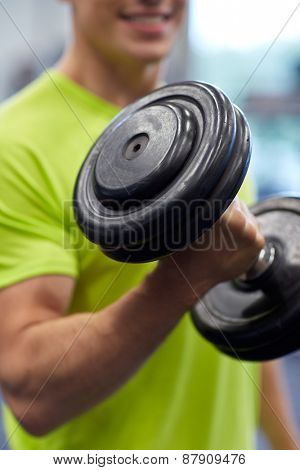 sport, fitness, lifestyle and people concept - close up of smiling man with dumbbell flexing biceps in gym