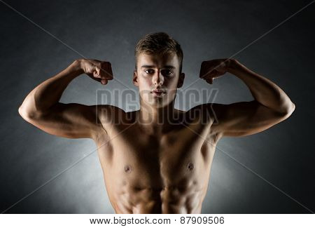 sport, bodybuilding, strength and people concept - young man showing biceps over black background