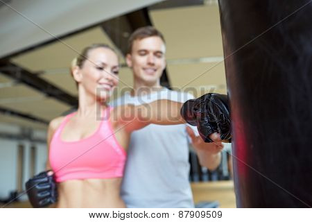 sport, fitness, lifestyle and people concept - happy woman with personal trainer boxing punching bag in gym