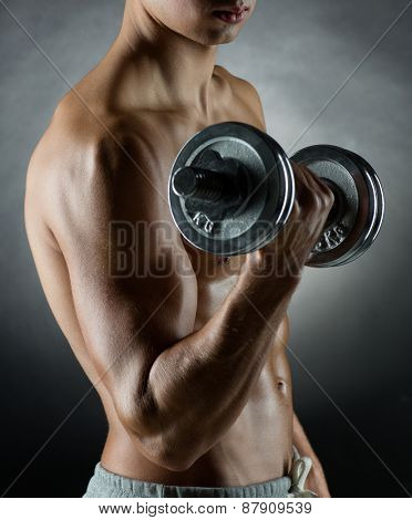 sport, bodybuilding, training and people concept - young man with dumbbell flexing muscles over gray background