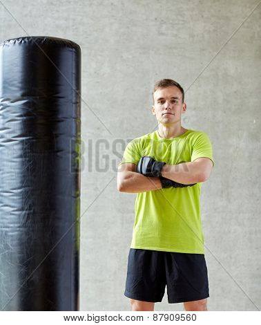 sport, box and people concept - young man with boxing gloves and punching bag in gym