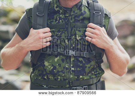 war, hiking, army, camouflage equipment and people concept - close up of young soldier or ranger with backpack in forest