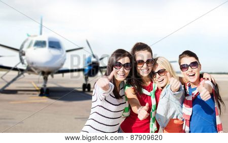 summer holidays, vacation, travel and people concept - happy teenage girls in sunglasses or young students showing thumbs up over airport background