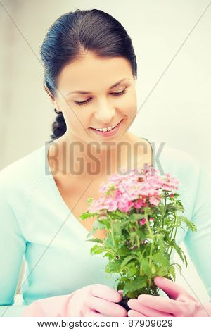 bright picture of lovely housewife with flower in pot
