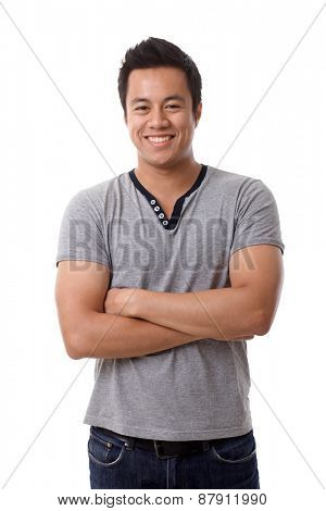 Happy young Asian man standing arms crossed smiling happy, looking at camera.