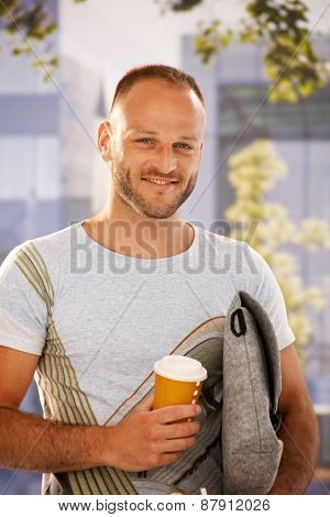 Closeup portrait of handsome young man holding bag and coffee in hands outdoors, smiling happy, looking at camera.