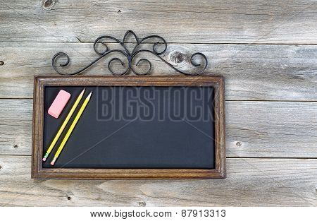 Old Chalkboard With Pencils And Eraser On Wood