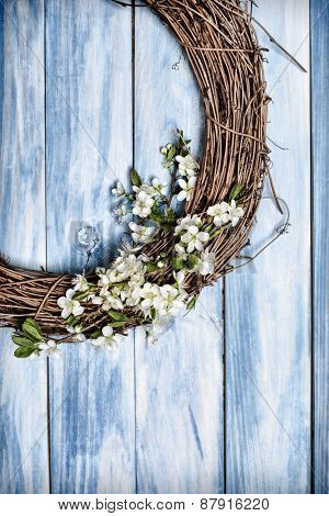 Spring apple blossom garland hanging on blue wooden door