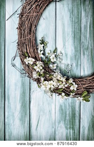 Springtime wreath filled with apple blossom on green wooden door